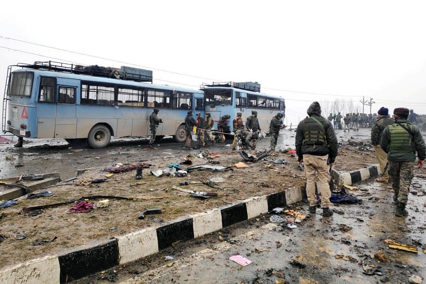 Indian soldiers examining debris after an explosion in Lethpora in south Kashmir's Pulwama district on Feb 14, 2019.