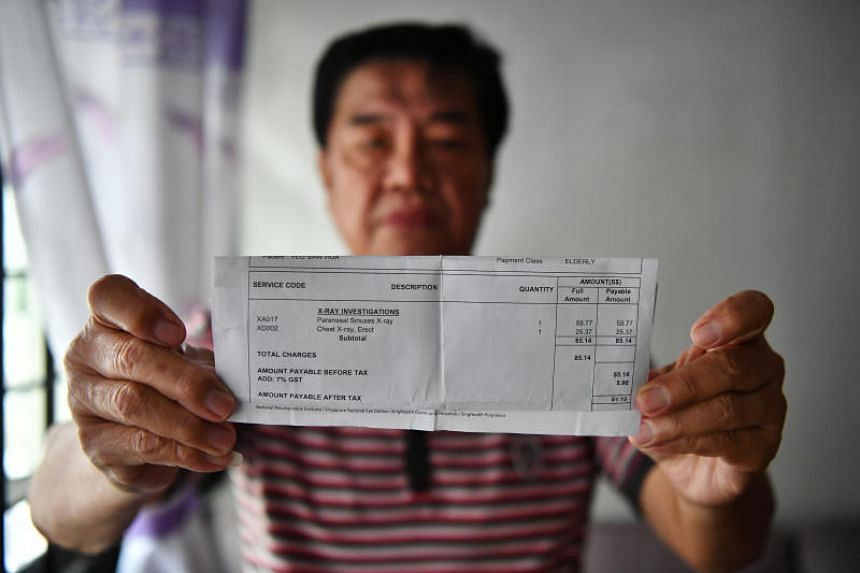 Part-time taxi driver Charlie Lim with his wife's polyclinic bill.