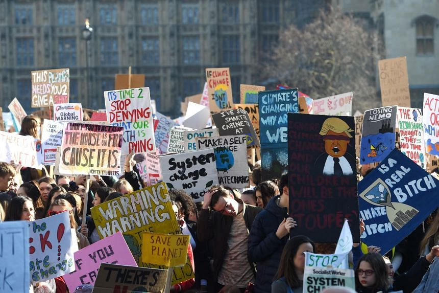 """Students hold placards and shout slogans as they take part in a climate change protest organised by """"Youth Strike 4 Climate"""", in Parliament Square, central London, on Feb 15, 2019."""