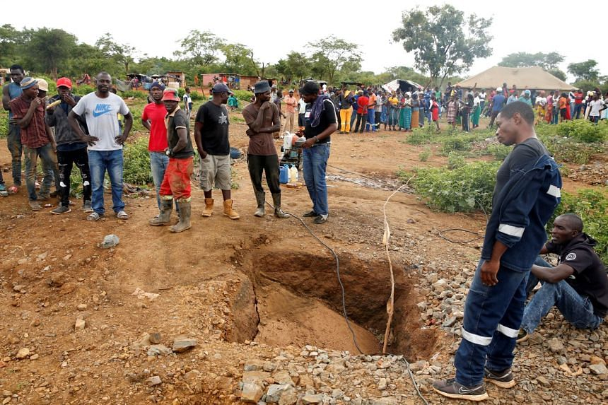 People gather over a shaft as retrieval efforts proceed for trapped illegal gold miners in Kadoma, Zimbabwe, Feb 15, 2019.