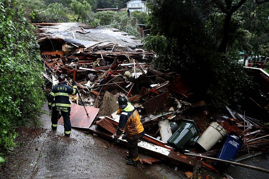 Southern Marin firefighters searching a home that was swept downhill by a mudslide during a rainstorm in Sausalito, California on Thursday. Fifty homes were evacuated after the mudslide struck homes and sent at least one sliding 70m down a hill. No i