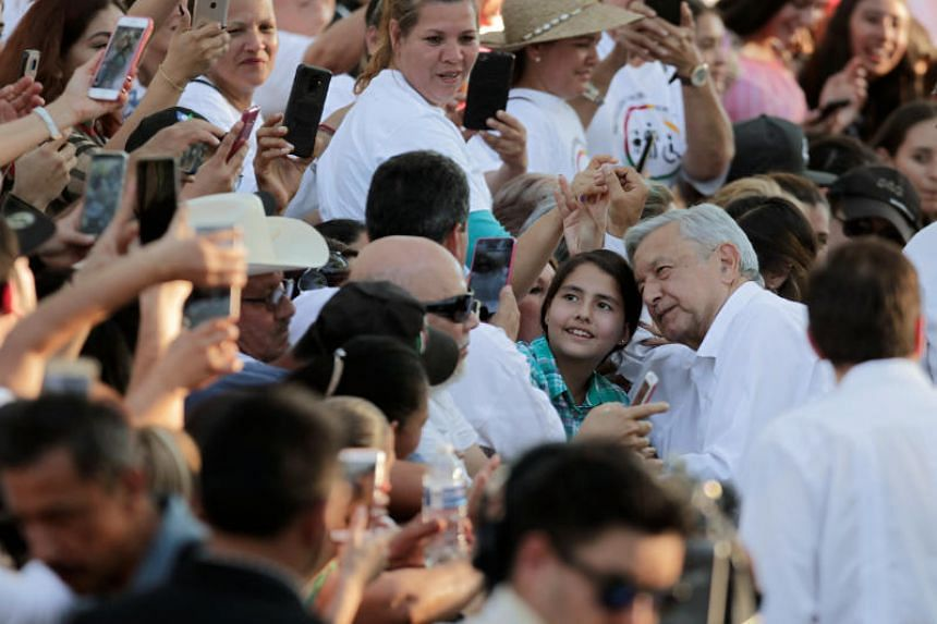 Mexico's President Andres Manuel Lopez Obrador poses for a photo with a child during his arrival to an event in Badiraguato, in the Mexican state of Sinaloa, Mexico on Feb 15, 2019.