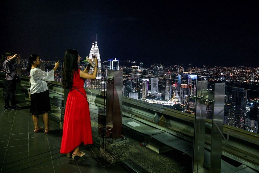 Tourists taking pictures of the city skyline from the observation deck of the Kuala Lumpur Tower in Kuala Lumpur, Malaysia, on Feb 14, 2019.