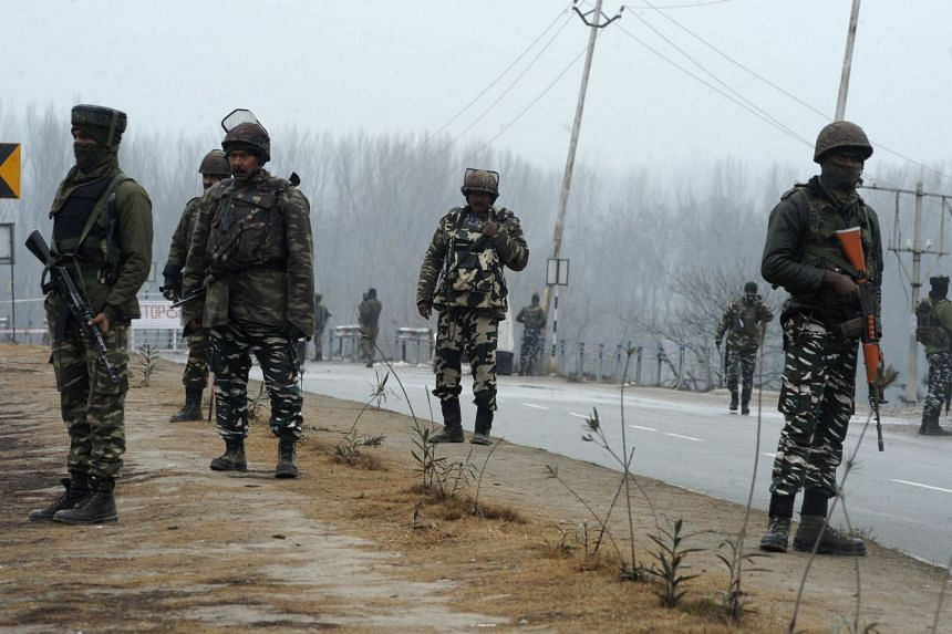 Indian security forces stand guard along the Jammu-Srinagar highway in Lethpora area in the town of Pampore the day after an attack on a paramilitary Central Reserve Police Force (CRPF) convoy in the Lethpora area of Kashmir.
