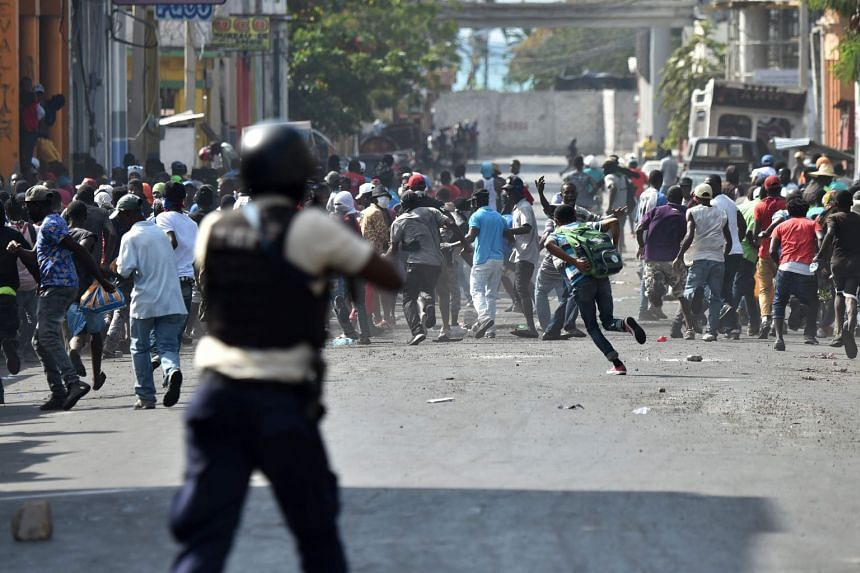 Demonstrators flee as Haitian Police open fire during clashes in Port-au-Prince.
