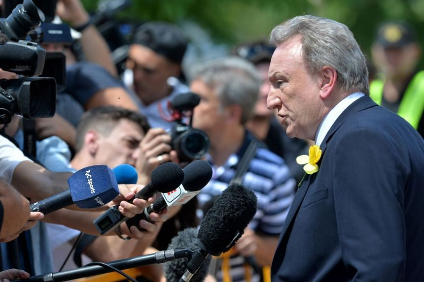Cardiff City manager Neil Warnock speaks with journalists as he attends the funeral.