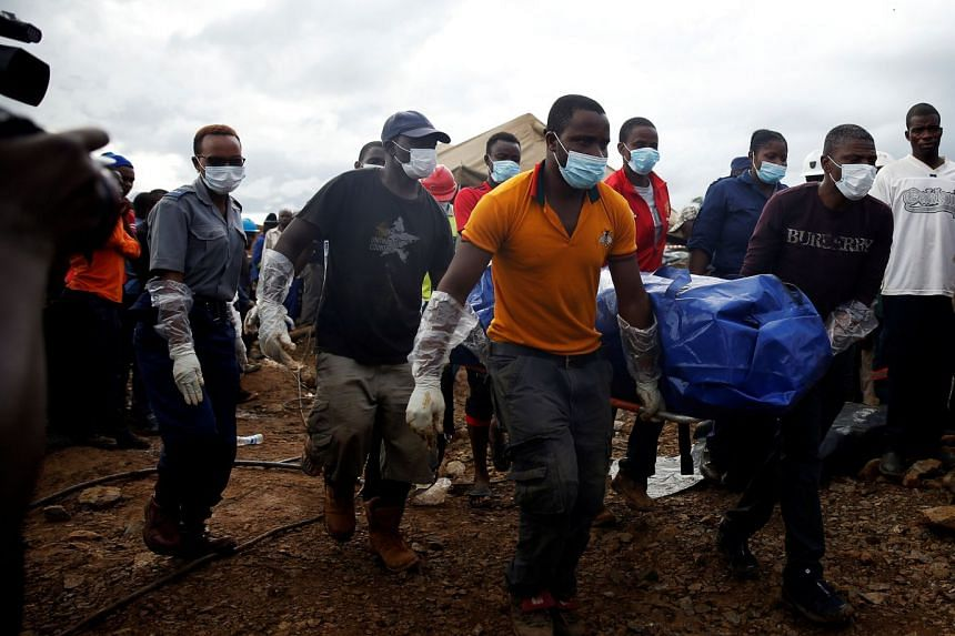 Rescue workers carry a body as retrieval efforts proceed for trapped artisanal gold miners near Kadoma, Zimbabwe.