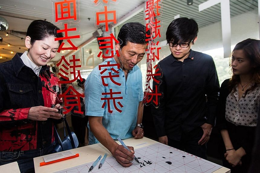 Education Minister Ong Ye Kung writing a message of well wishes for The Future of Our Pasts at the launch of the festival at Golden Mile Tower's The Projector yesterday. Looking on are (from left) Mr Gene Tan, executive director of the Singapore Bice