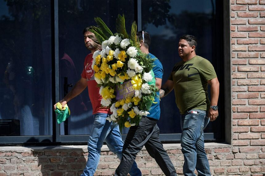 People carrying a wreath arrive to attend the wake of late Argentine football player Emiliano Sala.