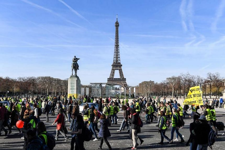 """People take part in a demonstration called by the """"yellow vest"""" movement on Feb17, 2019, near the Eiffel tower in Paris, to mark the third month of protests against the French President's policies and top-down style of governing, high cost of living"""