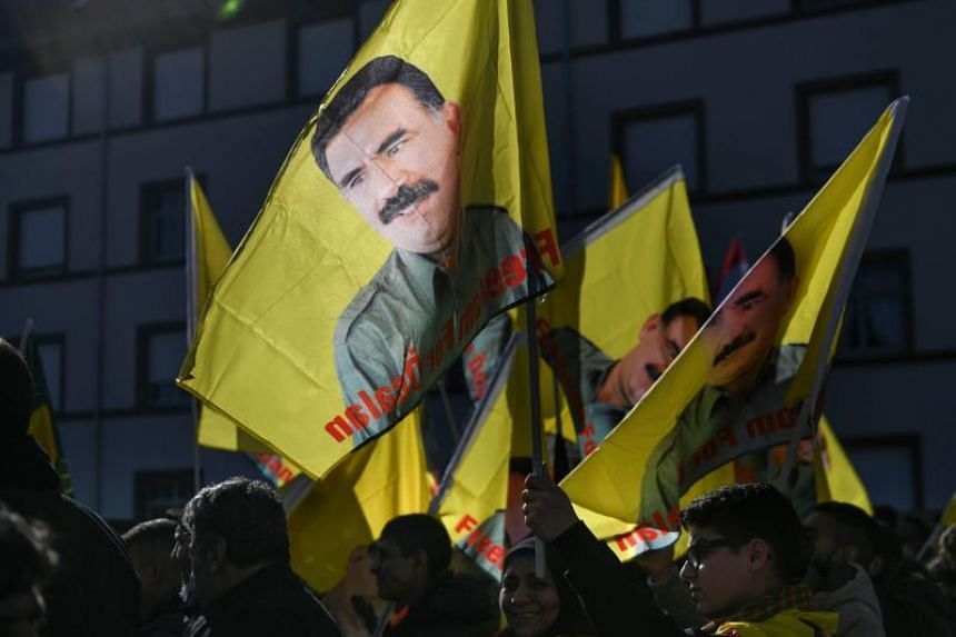 """People march with flags reading """"Freedom for Ocalan"""" during a demonstration in Strasbourg, eastern France to mark 20 years since the arrest of Kurdish leader Abdullah Ocalan, who is jailed in Turkey, on Feb 16, 2019."""