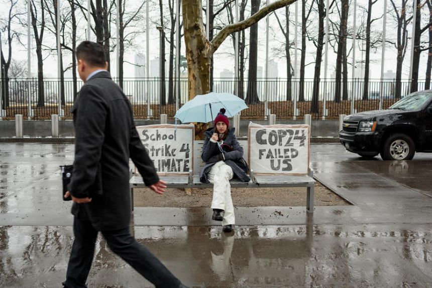 "Alexandria Villasenor demonstrating in front of the United Nations with signs reading ""School Strike 4 Climate"" and ""COP24 failed us""."