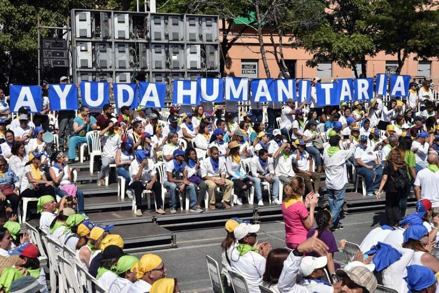 """Volunteers of the Aid and Freedom Venezuela Coalition holding up letters forming the words """"humanitarian aid"""" during a rally by Venezuelan opposition leader Juan Guaido in Caracas, on Feb 16, 2019."""