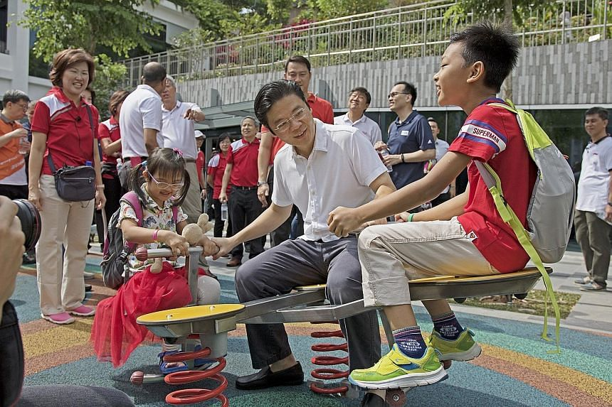 Minister for National Development Lawrence Wong with children on the rooftop of Oasis Terraces yesterday. The mall in Punggol has community gardens and a fitness corner on the roof, as well as 106 shops.