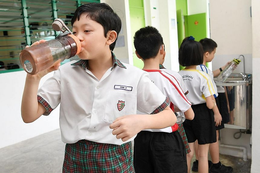 "Above: Madam Yvonne Kong, whose two children, Gabriel and Natalie, are studying at Jurong West Primary, is relieved that the school does not have a drink stall. ""They can pick up the habit of drinking water instead of sugary drinks,"" she says. Right:"