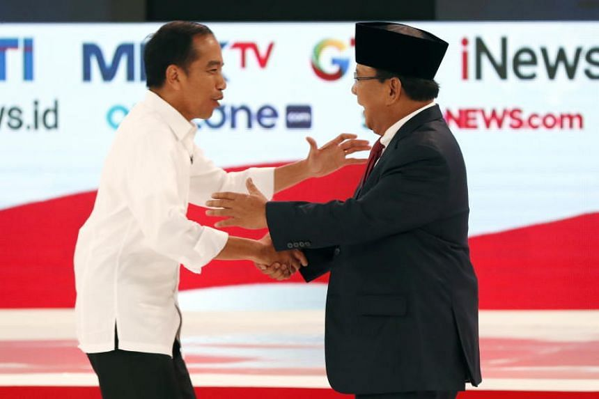 Presidential candidates Joko Widodo (left) and Prabowo Subianto shake hands during a debate among candidates in Jakarta, Indonesia, on Feb 17, 2019.