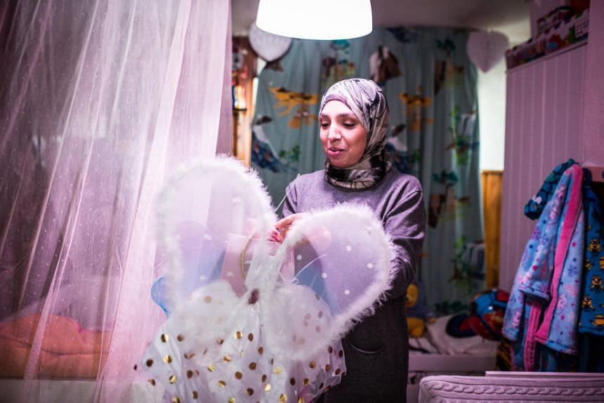 Fatiha, a Belgian whose grandparents emigrated from Morocco, looks at a dress that she bought for a granddaughter at her home in Ranst, Belgium.