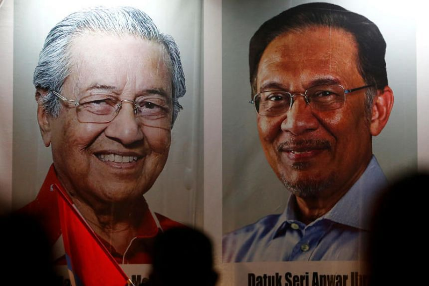 People pass by posters of Malaysian Prime Minister Mahathir Mohamad (left) and politician Anwar Ibrahim in Kuala Lumpur, Malaysia, on May 16, 2018.