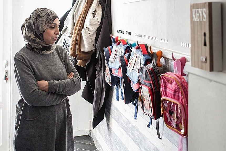 "Ms Fatiha looking over the backpacks she has prepared for her six grandchildren at her home in Ranst, Belgium. A ""Spider-Man"" bedsheet and teddy bears (far left) on one of the beds she has ready. But there is no knowing if and when the children - now"
