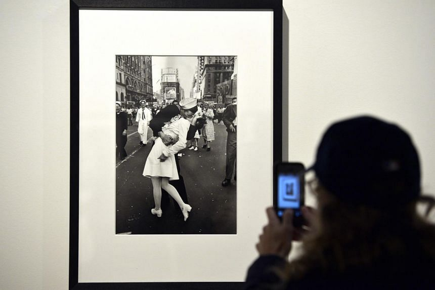 A visitor takes a snapshot of the iconic image, V-J Day in Times Square, by Alfred Eisenstaedt.