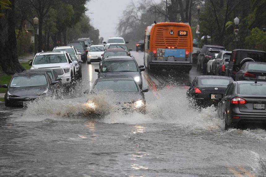 Cars drive through a flooded street after a storm dumped heavy rain on Los Angeles, on Feb 2, 2019.