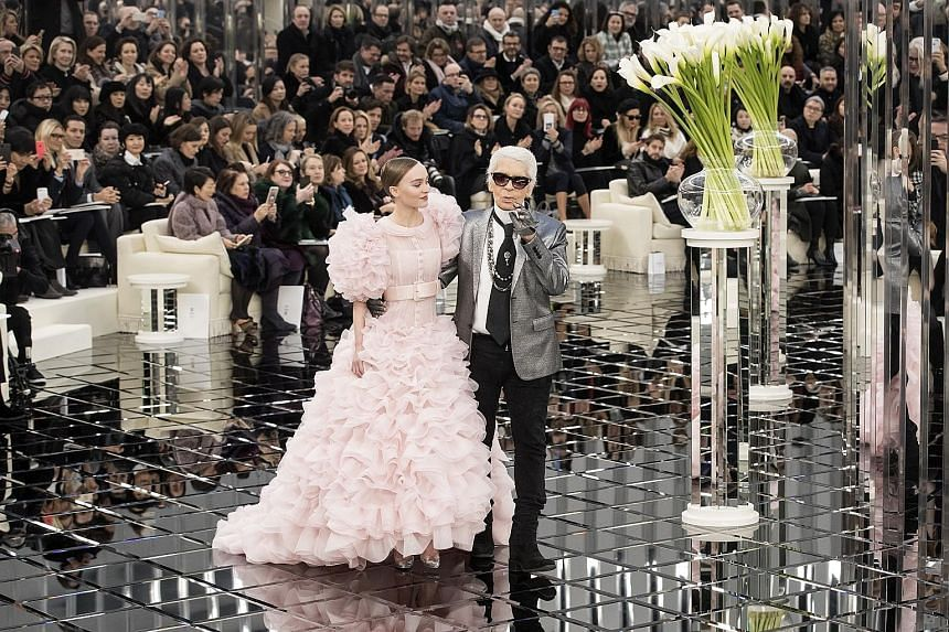 German designer Karl Lagerfeld on the catwalk with US-French model Lily-Rose Depp after the spring/summer 2017 haute couture collection show for Chanel during Paris Fashion Week Floral tributes seen placed outside the French fashion house Chanel in P