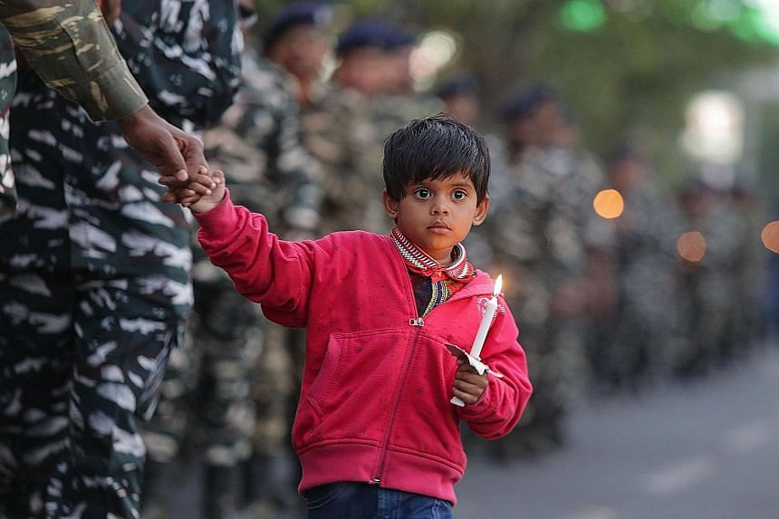 An Indian boy joining mourners paying their last respects to the Central Reserve Police Force troopers during a candlelight march in Bhopal last Saturday. Indian Muslims holding up a scratched photo of Pakistan-based terror group chief Masood Azhar a