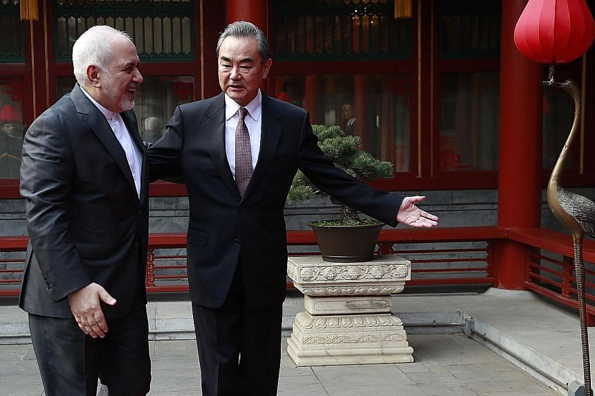 Chinese Foreign Minister Wang Yi showing Iranian counterpart Mohammad Javad Zarif around the state guesthouse in Beijing yesterday. China has had to walk a fine line, maintaining close ties with both Saudi Arabia and Iran.