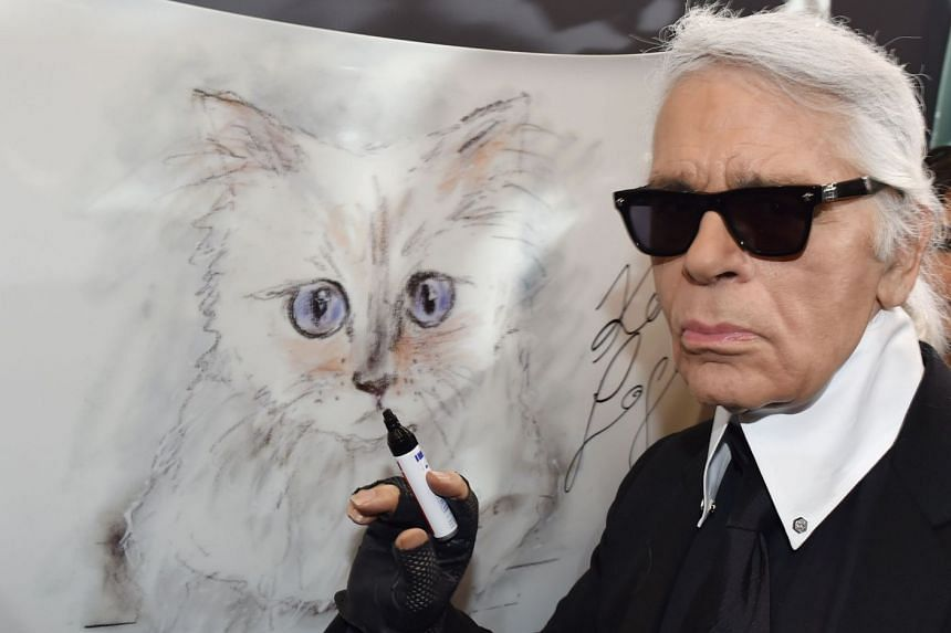 """Lagerfeld posing next to a painting of his cat """"Choupette"""" in 2015."""