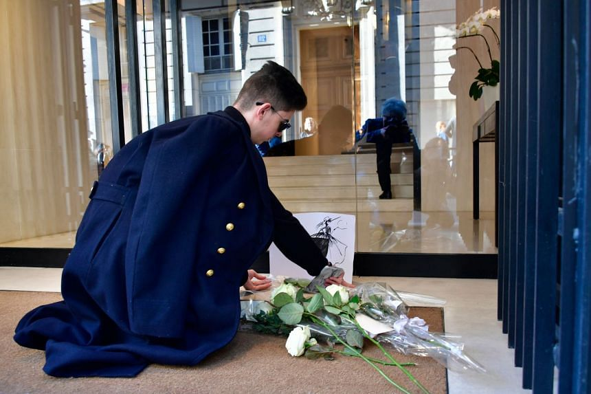 A man lays flowers in tribute to late German fashion designer Karl Lagerfeld outside Chanel in Paris.