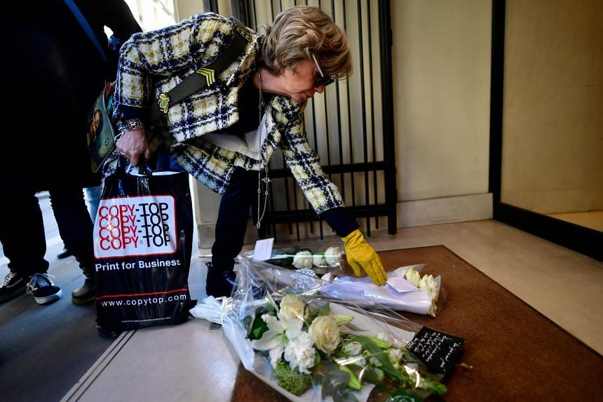 A woman lays flowers in tribute to Karl Lagerfeld outside Chanel in Paris.