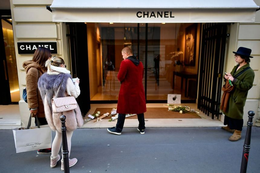 People stand in front of flowers laid in tribute to Karl Lagerfeld outside Chanel in Paris.