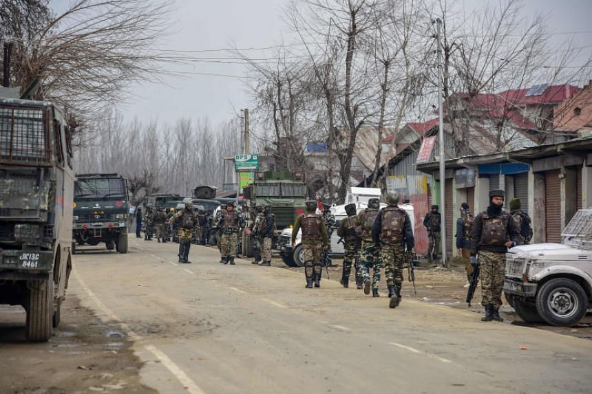 Indian paramilitary troopers patrol at the scene of a gun battle with suspected militants in Pulwama.