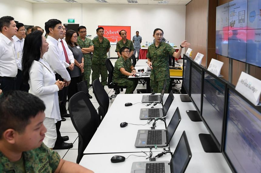 Senior Minister of State for Defence Heng Chee How (front row, second from left) listening to a presentation at the Cyber Defence Test and Evaluation Centre.