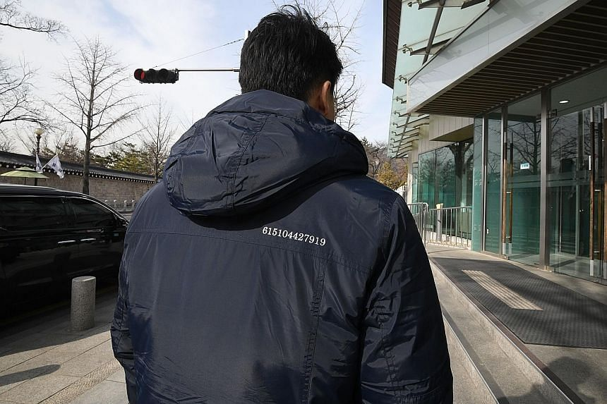 One of South Korea's Blue House security officers wearing a jacket with 12 numbers - 615104427919 - sewn onto the back. The digits stand for key moments in inter-Korean ties.