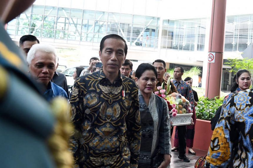 Indonesian President Joko Widodo (centre), his wife Iriana Widodo (right) and Former Minister Hatta Rajasa arrive at the National University Hospital on Feb 21, 2019.