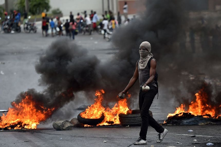 A demonstrator walks next to barricades during clashes with Haitian police in Port-au-Prince, on Feb 15, 2019.