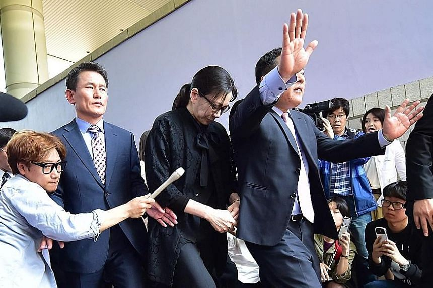"""Korean Air executive Cho Hyun-Ah (centre) after she received a suspended jail sentence from a court in Seoul, in May 2015, over her """"nut rage"""" tantrum on board a plane the year before. Cho's husband has accused her of abusing him and their young chil"""