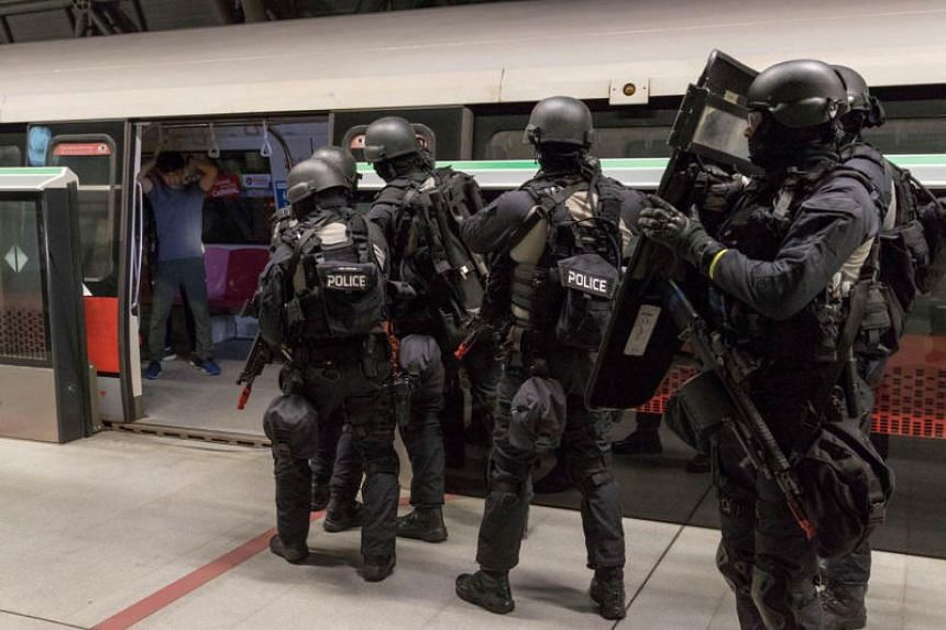 """The police's Armed Strike Team engaging """"gunmen"""" at the train platform of Tuas Link MRT station in a counter-terrorism exercise on Feb 22, 2019."""