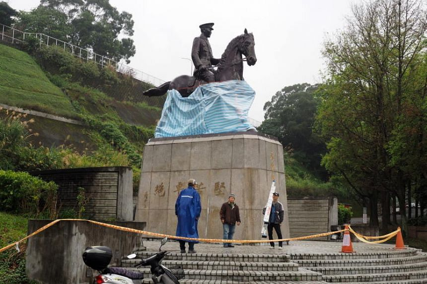 Men use tarpaulin to cover up the vandalized statue of late president Chiang Kao-shek at the National Chengchi University in Taipei, Taiwan on Feb 22, 2019.