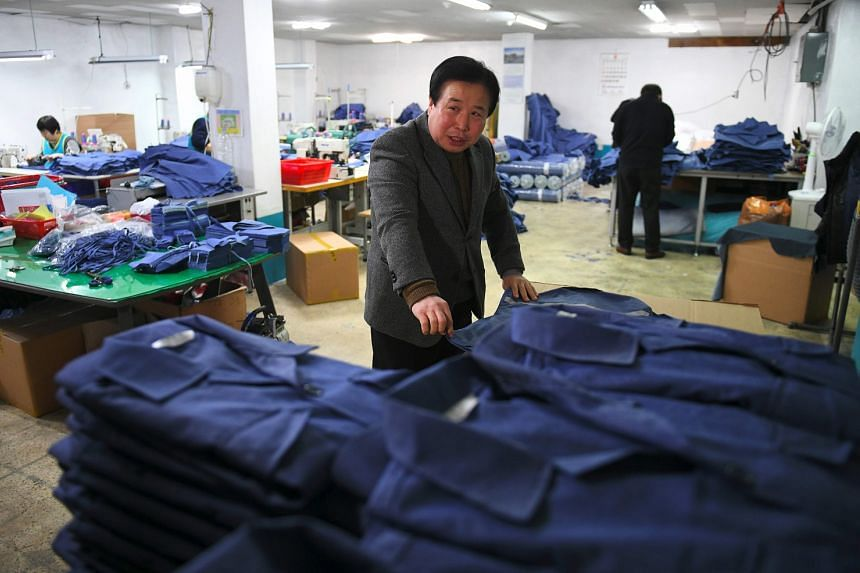 South Korean businessman Park Yong-man checking uniforms produced in the basement of his Seoul office. It has been three years since his factory in the Kaesong Industrial Complex was shuttered amid soaring tensions. His textile company, which employe