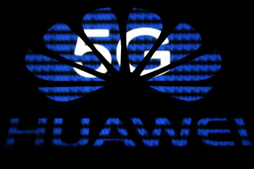 A 3-D printed Huawei logo in front of displayed 5G words in this illustration.
