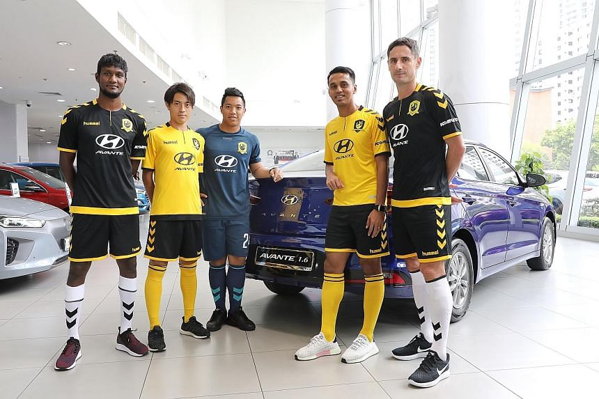 Tampines Rovers players posing beside the Hyundai Avante at the Hyundai Showroom yesterday. Komoco Motors will be the new sponsor of SPL club Tampines Rovers.