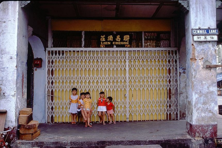 Children outside a shuttered shop in Gemmill Lane, in the Telok Ayer area, 1977. The many local scenes captured by Mr Paul Piollet (right) include (far right) that of people young and old being enraptured by an opera performance in Chin Nam Street, 1