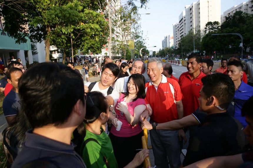 Prime Minister Lee Hsien Loong taking photos with residents as he arrives for the street parade.