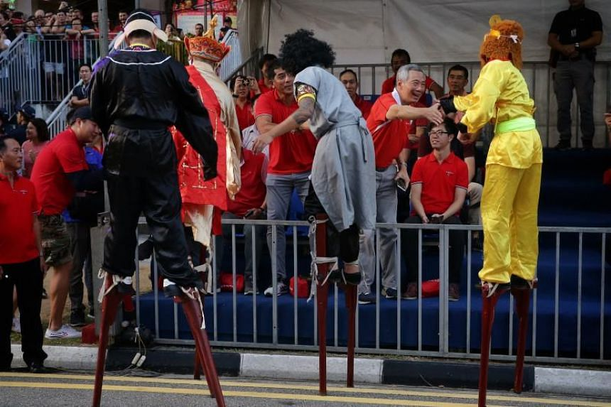 Prime Minister Lee Hsien Loong shaking hands with stilt walkers dressed up as characters from Journey to the West during the Ang Mo Kio - Hougang Chinese New Year Street Parade.