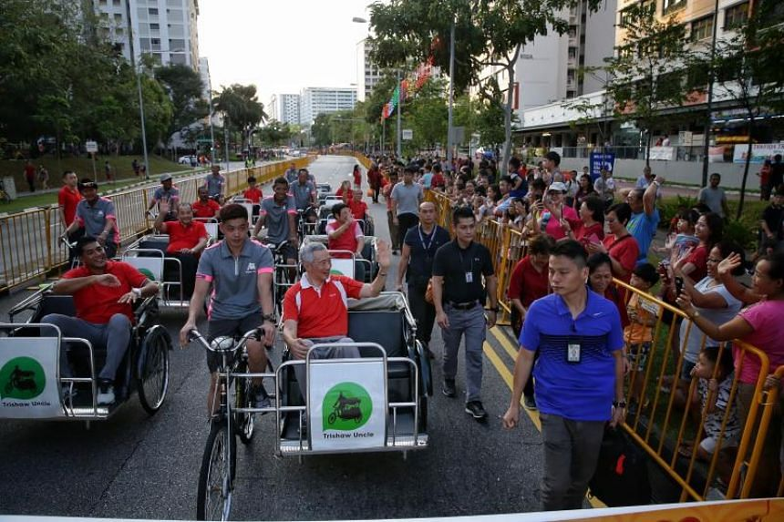Prime Minister Lee Hsien Loong waving to residents as he takes a ride on a trishaw at the Ang Mo Kio - Hougang Chinese New Year Street Parade along Hougang Avenue 9, on Feb 23, 2019.
