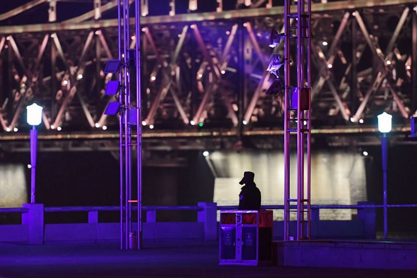 A policeman patrols at the cordoned-off waterfront area near the Sino-Korean Friendship Bridge (top) shortly before the arrival of the armored train of North Korean leader Kim Jong Un.