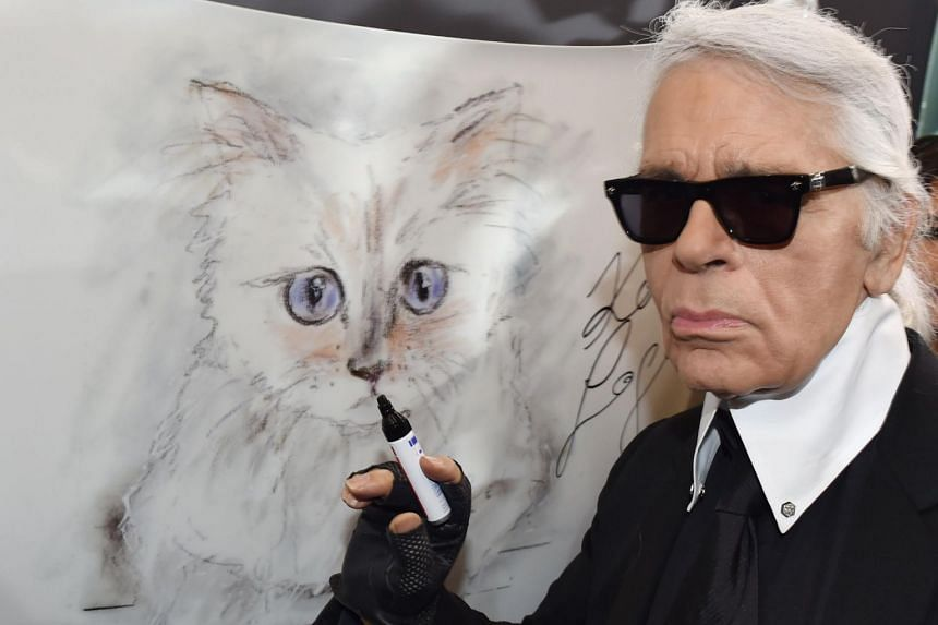 Karl Lagerfeld poses next to a painting of his cat Choupette during the inauguration of the show Corsa Karl and Choupette at the Palazzo Italia in Berlin, on Feb 3, 2015.