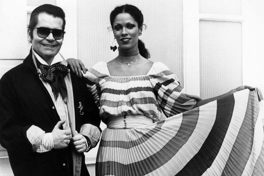 Karl Lagerfeld poses next to a model presenting a dress from his Chloe collection on May 2, 1977 in Hamburg.